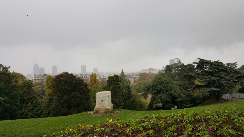flower bed and green lawn at front of picture, bushy trees and behind them glimpses of paris buildings and skyscrapers.  Dark cloudy sky.