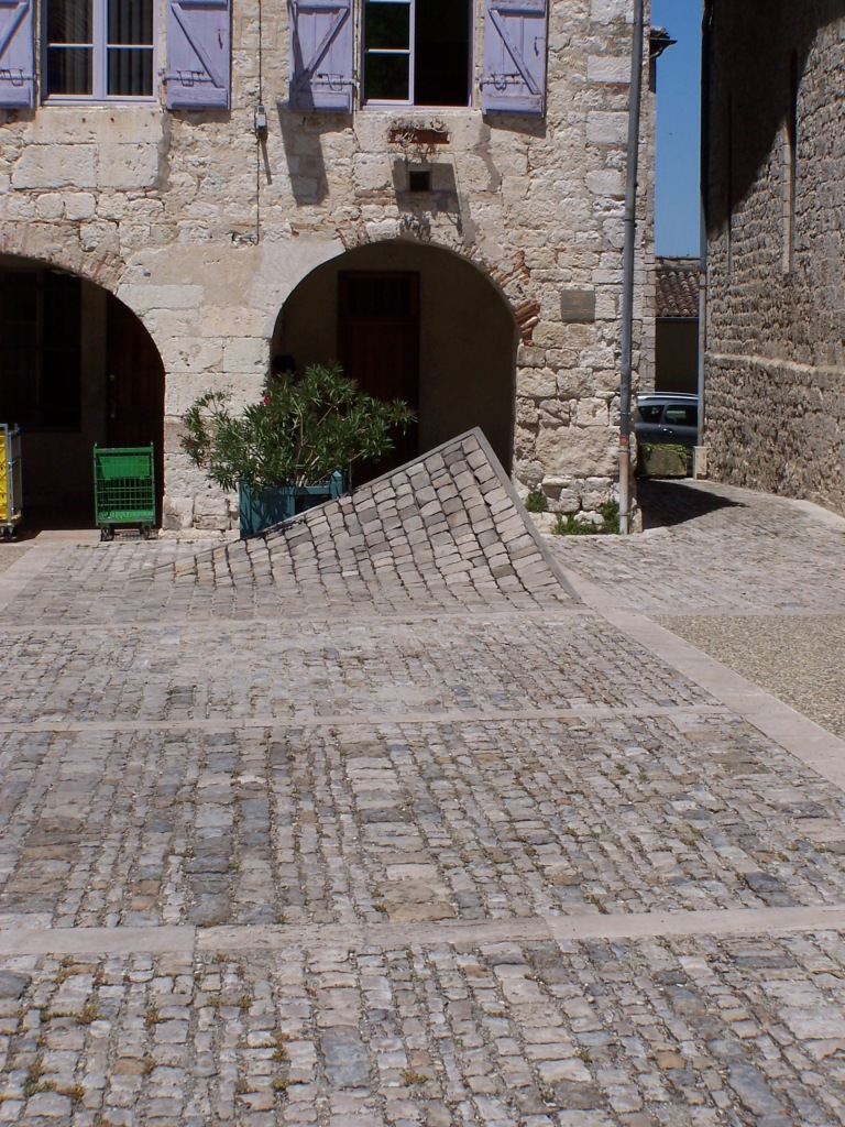cobbled ground in front of buildings, one corner raised like a carpet.