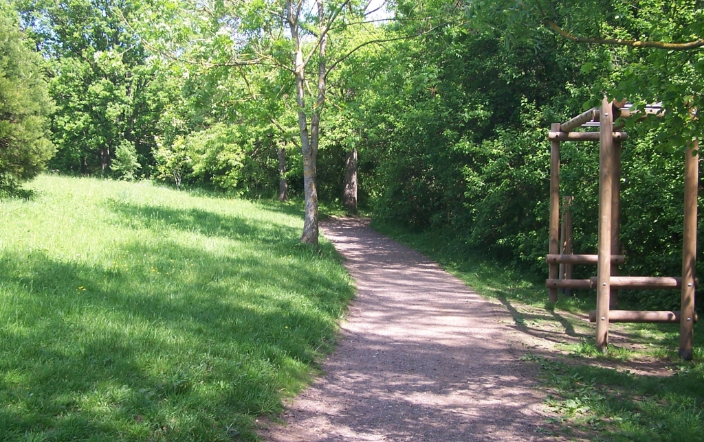 Green bank on left, wide gravel path in centre, trees to right, bright sunshine